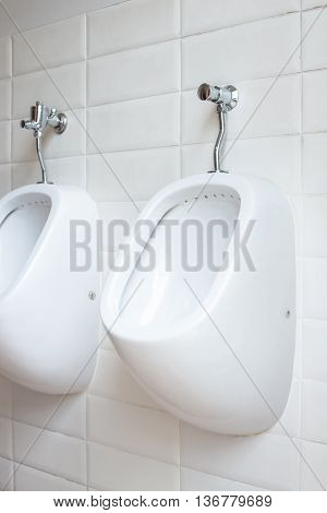 White urinals men in public toilet mounting on the wall