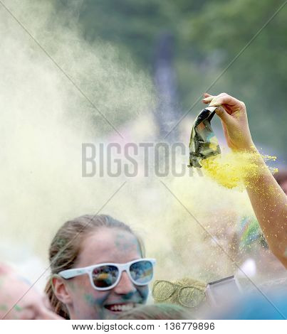 STOCKHOLM SWEDEN - MAY 22 2016: Crowd of happy people covered with color powder squirting yellow powder in the Color Run Event in Sweden May 22 2016