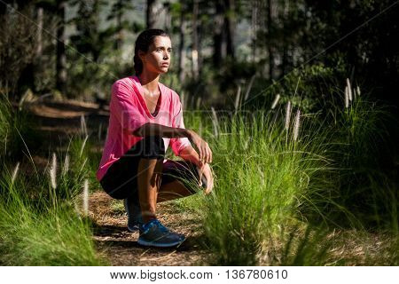 Woman unsmiling posing squat on the wood