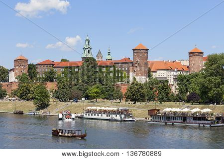 KRAKOW POLAND - JULY 02 2016 : View on Wawel Royal Castle river boats and Vistula boulevards . Place often visited by tourists and locals for purposes of relaxation on sunny days.