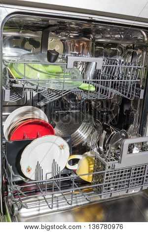 Opened dishwasher with clean shiny different dishes.
