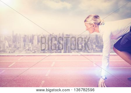 Businesswoman in the starting blocks against composite image of racetrack in city