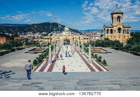 Tbilisi Georgia - July 18 2015. Tourists visits area of Holy Trinity Cathedral main cathedral of the Georgian Orthodox Church in Georgia