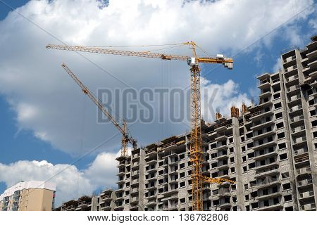 New high-rise modern apartment buildings construction in process on bright sunny day front view horizontal