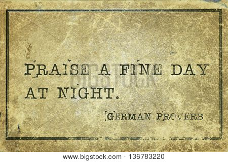 Praise a fine day at night - ancient German proverb printed on grunge vintage cardboard
