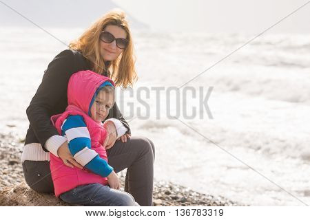 My Mother And Five Year Old Daughter Sit On The Beach And Looked At Turning Frame