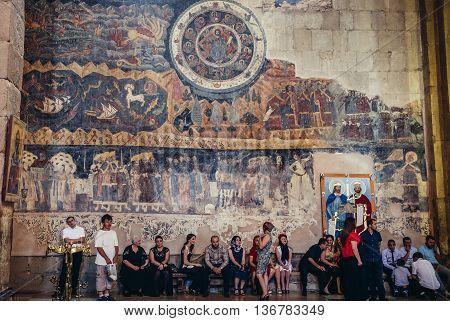 Mtskheta Georgia - July 18 2015. People sits on a bench in Svetitskhoveli Cathedral of Georgian Orthodox Church in Mtskheta one of the oldest cities in Georgia