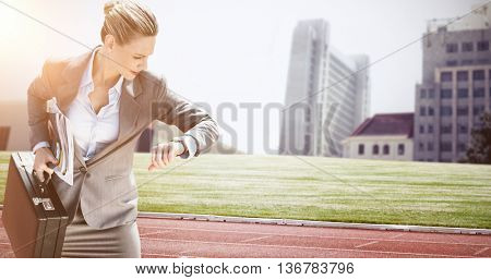 Businesswoman looking at her watch against composite image of racetrack in city