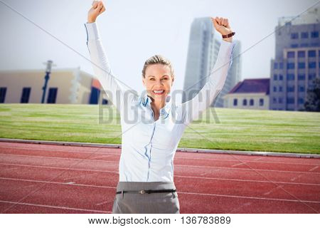 Successful businesswoman raising arms against composite image of racetrack in city