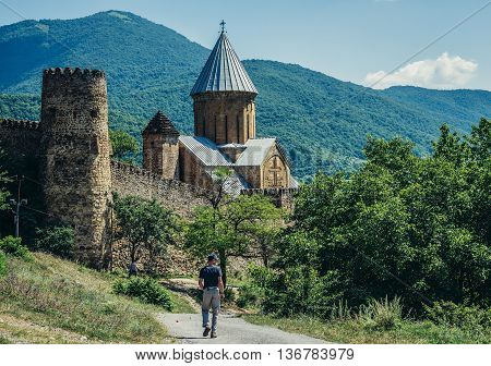 Ananuri Georgia - July 20 2015. Tourists walks down the path to Ananuri Castle with Church of the Assumption in Georgia
