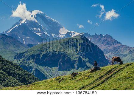 Gergeti Georgia - July 20 2015. Tourist sits on a rock view with Kazbek Mountain near Gergeti village in Caucasus Mountains Georgia