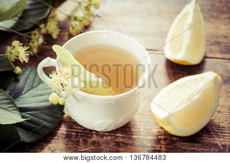 Tea with linden and lemon in a cute white porcelain cup on rustic wooden table. Healthy drink to boost immune system, stabilize blood pressure and helps to fight flue.