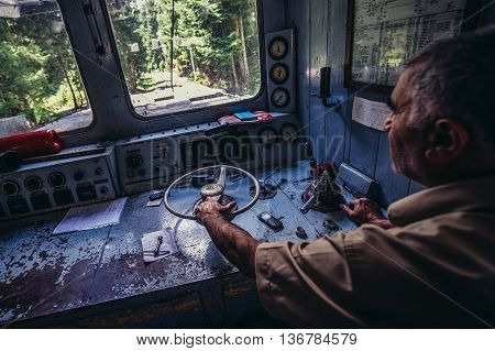 Georgia - July 22 2015. Engine driver drives old Skoda electric engine of Borjomi-Bakuriani narrow gauge railway known as