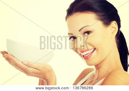 Attractive fit woman holding white bowl