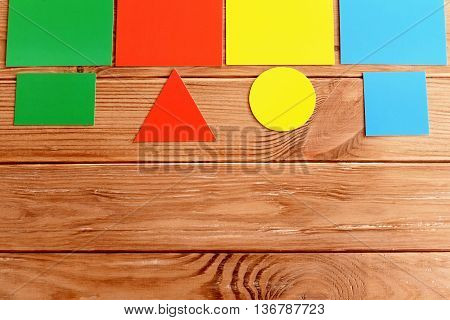 Paper cards to teach children colour and shape. Cardboard square, triangle, rectangle and circle near by corresponding color cards. Kids early learning concept. Wooden background. Top view