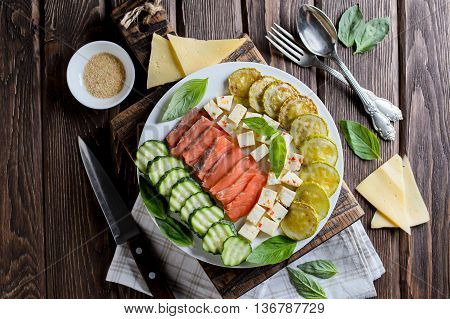 Plate with the fried vegetable marrows salmon salad on rustic table cutting