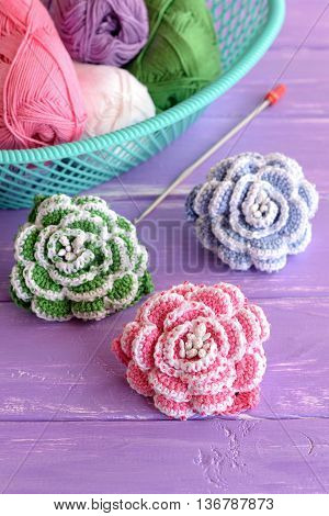 Pink, green and blue crochet flowers decorated with beads. Cotton yarn skeins in basket, hook and bright knitted roses on lilac wooden background. Beautiful beaded crochet project