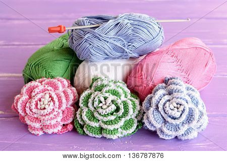 Pink, green and blue crochet roses decorated with beads. Cotton yarn skeins, hook and bright knitted flowers on wooden background lilac. Home decor crochet project