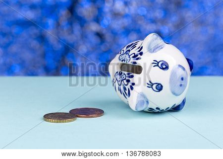 White piggy bank on a blue background: it's on its side with a few penny's, a concept of a tight budget