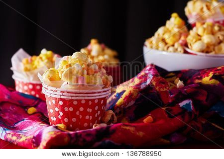 A red paper cup with popcorn against black background with spot lighting,shallow Depth of Field,Focus on popcorn.