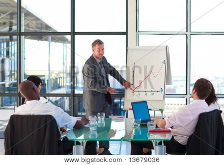 Senior businessman reporting to graphs in a presentation with his colleagues