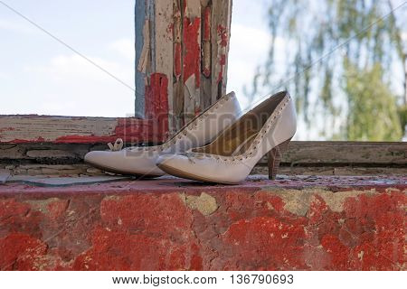 White High Women's shoes in the window of an abandoned building