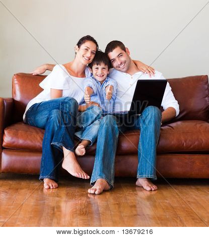 Son and parents playing with a laptop and smiling at the camera