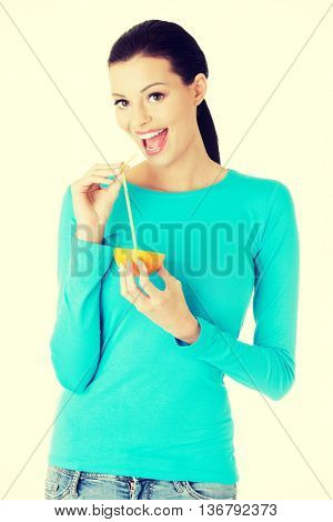 Woman drinking orange juice straight from fruit