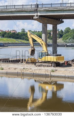 Yellow excavator on the construction site to build a new bridge.