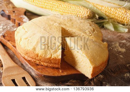 Round Loaf Of Corn Bread Close-up On A Wooden Board. Horizontal