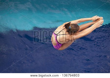 Lady springboard diver jumping into the swimming pool
