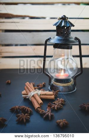 still life of candlestick cinnamon star anise and maple seeds