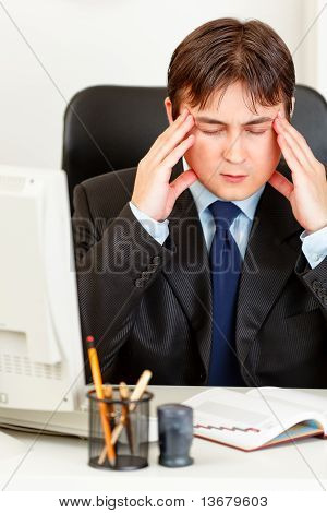 Tired modern business man sitting at office desk