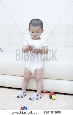 Cute Chinese Baby Boy Playing A Mobile Phone In Sofa