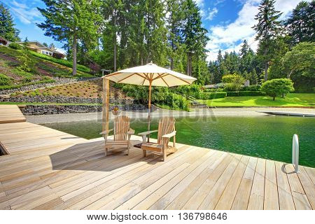 Two Adirondack Wooden Chairs With Umbrella On Dock Facing Beautiful Landscape.