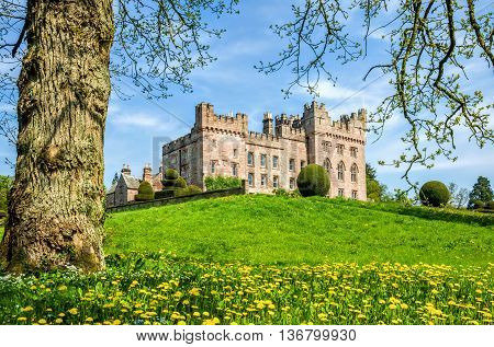 Green lawn in front of Hutton in the Forest castle in Cumbria, England on sunny day with blue skies.