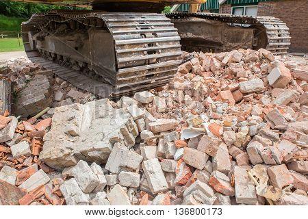 Metal caterpillars on heap of broken bricks of demolished house