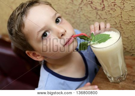 Child drinking milk shake in a cafe