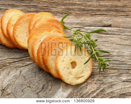 Dry rolls bread with herb on wooden background