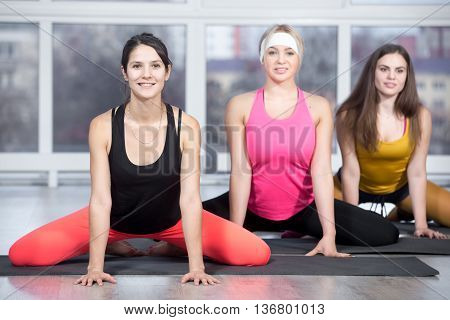 Fitness stretching practice group of three beautiful happy fit young people in colorful sportswear working out in sports club doing exercises for thighs and groins in gym