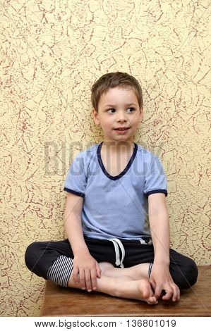 Child sitting on wooden commode on wall background