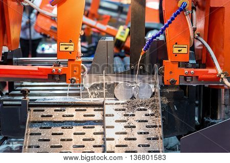 Steel band saw machine working in industry factory.