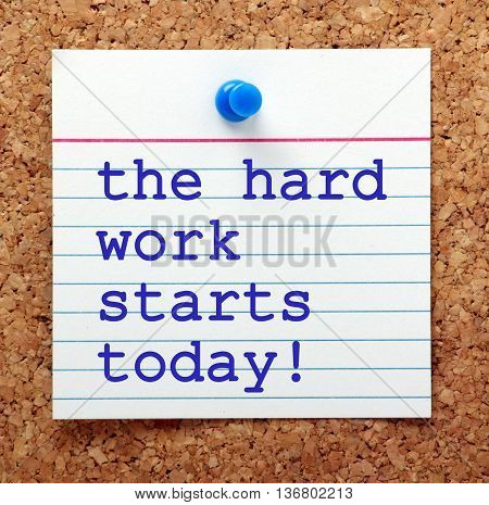 The words The Hard Work Starts Today in blue text on a note card pinned to a cork notice board for motivation