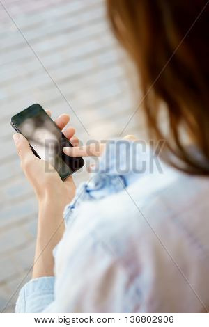 Brunette woman holding smartphone and touching finger on screen. Photo taken over shoulder. Taken with fast aperture