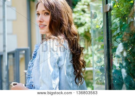 Portrait of dark haired beautiful woman in profile on summer green street background