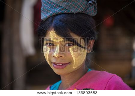 MRAUK-U MYANMAR - JANUARY 27 2016: Unidentified young Myanmar girl with thanaka on her smile face is happiness. Thanaka is a yellowish-white cosmetic paste made from ground bark.
