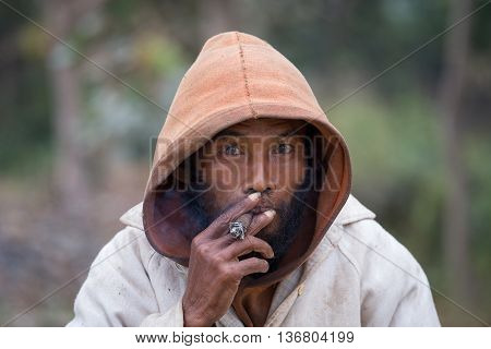 MRAUK-U MYANMAR - JANUARY 27 2016: Portrait of an unknown beggar who smokes a cigarette outdoors