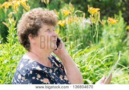 curly-haired woman with a cell phone and tablet outside