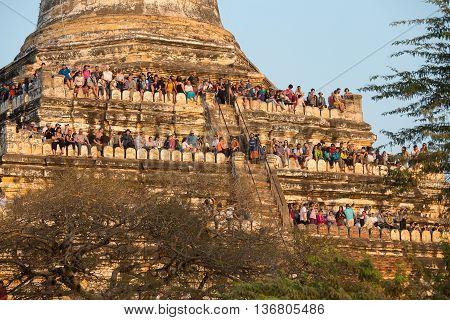 BAGAN MYANMAR - JANUARY 20 2016: Unidentified tourists climbed to the pagoda to take pictures of the sunset over Bagan