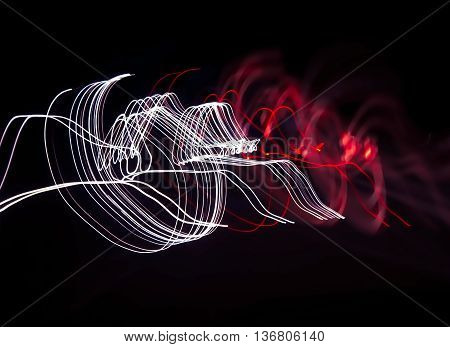 Waves of red and white light on black background. Design background or abstract background with copy space.